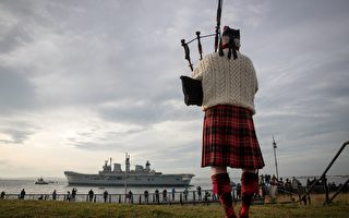 PORTSMOUTH, ENGLAND - DECEMBER 07:  Piper Larry Cunningham plays his bagpipes as Britain's last serving aircraft carrier HMS Illustrious is towed from her home port at Portsmouth Docks after being sold for scrap on December 7, 2016 in Portsmouth, England. The 22,000 tonne ship, whose service started in 1982 in the aftermath of the Falklands War and saw deployments in Bosnia and Sierra Leone, was affectionately known as 'Lusty' and will be broken up for scrap in Turkey despite attempts last minute attempts to save her.  (Photo by Matt Cardy/Getty Images)