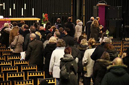 在事发地点旁边的纪念教堂里,人们排队等待在教堂留言簿上写下自己的感想。(Sean Gallup/Getty Images)