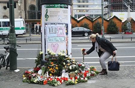 在遭受卡车恐袭的柏林圣诞市场的入口处,柏林市民在次日点燃蜡烛,献上鲜花,以表悼念。(Sean Gallup/Getty Images)