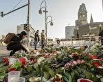 12月21日,在柏林Breitscheidplatz广场上的圣诞市场附近,人们在地上放上了无数支蜡烛,一束束鲜花点缀其中。两天前,一辆卡车以60多公里的时速冲进圣诞广场,12人死亡,近50人受伤。警方声明这是一次恐怖袭击。凶手司机尚未抓获。(CLEMENS BILAN/AFP/Getty Images)