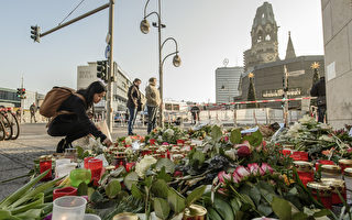 12月21日,在柏林Breitscheidplatz廣場上的聖誕市場附近,人們在地上放上了無數支蠟燭,一束束鮮花點綴其中。兩天前,一輛卡車以60多公里的時速衝進聖誕廣場,12人死亡,近50人受傷。警方聲明這是一次恐怖襲擊。凶手司機尚未抓獲。(CLEMENS BILAN/AFP/Getty Images)