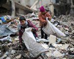 在土耳其和俄罗斯的斡旋下,叙利亚政府军同反抗军达成了全国停火协议,将于当地时间30日零点实现停火。图为叙利亚男孩从建筑倒塌的废墟中捡木材,用于生火取暖和做饭。(AMER ALMOHIBANY/AFP/Getty Images)
