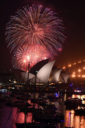 A family fireworks illuminates the sky above the iconic Opera House in Sydney on December 31, 2016, ahead of New Years fireworks. / AFP / SAEED KHAN (Photo credit should read SAEED KHAN/AFP/Getty Images)