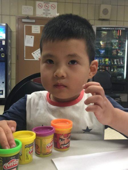 警员把走失的3岁华裔儿童带回警局,帮其找父母,并提供玩具给他玩,孩子很安静。