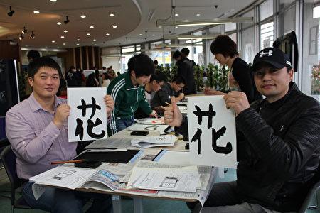 日本廣島市留學生會館於12月17日為留學生主辦「日本文化博覽會」。圖為來自蒙古國的步瑪(左)和朋友體驗書法 。(曉玥/大紀元)