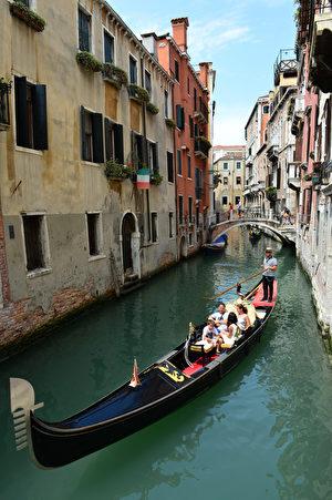 有着低调华丽的黑色船身,船夫站在船尾滑动并高声歌唱,这就是威尼斯独有且别具代表性的贡多拉。(OLIVIER MORIN / AFP)