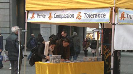 比利时民众支持法轮功,在制止中共迫害法轮功的请愿信上签字 。(新唐人)