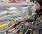 拥有2300万人口的台湾共有1万多家便利商店,平均每2300人就有一家,密集度傲冠全球。图为一名顾客在超商内选购食品。( AFP PHOTO / Sam YEH )