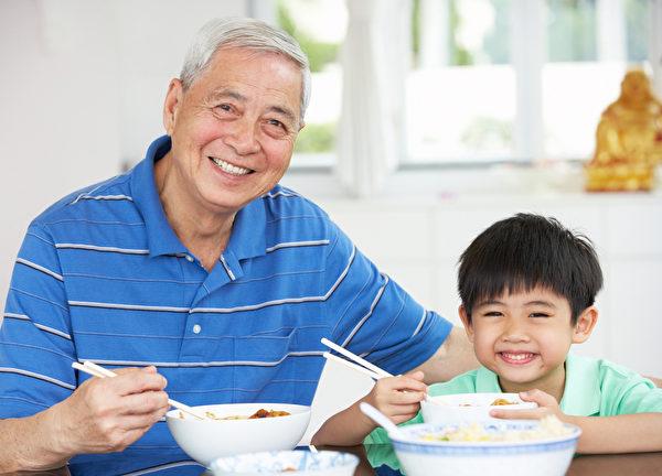 中国肖像爷爷和孙子在吃饭在一起(fotolia)