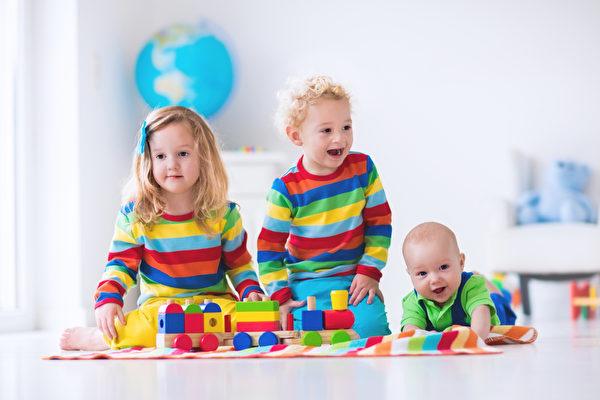 孩子们用木制玩具火车玩(fotolia)