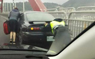 新北市淡水區關渡橋3日大塞車,1輛轎車在橋上拋錨,造成後方回堵。員警到場救援,協助將車輛往前推500公尺,網友直呼「警察辛苦了」。(警方提供)