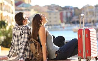 兩個遊人的側視圖有手提箱坐的放鬆和享受在五顏六色的散步的假期。 旅遊概念(fotolia)