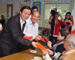 捐赠仪式后,五育高中董事长黄添荣(右)和草屯镇长洪国浩(左)一起分送红包给独居老人们。(黄淑贞/大纪元)