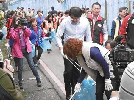 市长林右昌(前站立者)与议长宋玮莉(前弯腰者)带领志工沿途捡垃圾。(陈秀媛/大纪元)