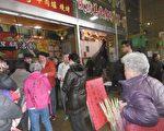 林右昌(中、穿红衣服)在成功市场门口让民众自行排队领红包。(陈秀媛/大纪元)