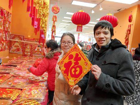 美国华人夫妇陈先生和太太逛年货市场,买对联和福字。 (于佩/大纪元)