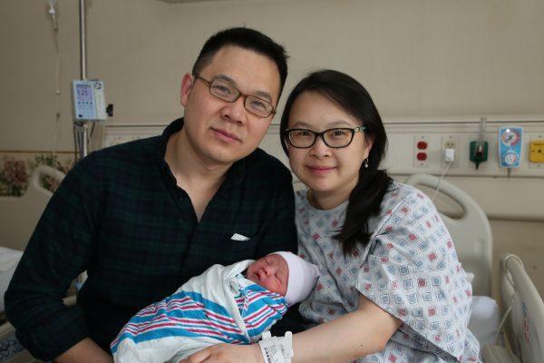 皇后医院华裔新年宝宝Raiden(中)的父母和宝宝在一起。 (林丹/大纪元)