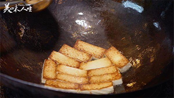 豆腐一翻面 趁热加盐(新唐人提供)