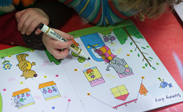 RADSTOCK, UNITED KINGDOM - JANUARY 06: A young girl draws at a playgroup for pre-school aged children in Chilcompton near Radstock on January 6, 2015 in Somerset, England. Along with the health and the economy, education and childcare are to be key issues in the forthcoming election. (Photo by Matt Cardy/Getty Images)
