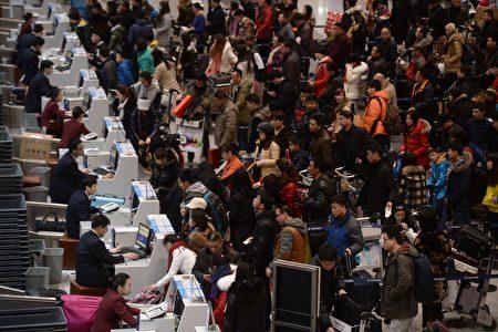 今年1月28日是中国新年,虽然这是中国家庭团聚的日子,但今年有更多的中国人选择出境旅行,以躲避阴霾。图为北京国际机场2015年2月中国新年大批旅客办理出境的情景。(STR/AFP/Getty Images)