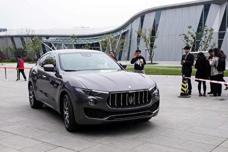 "This photo taken on March 23, 2016 shows people taking photos of a Maserati Levante sport-utility vehicle in Hangzhou, eastern China's Zhejiang province. Chinese drivers are rushing to buy sport-utility vehicles in an ""arms race"" for safety on the country's hair-raising roads, analysts say, as SUV sales hit the gas despite a slowing economy. / AFP / STR / China OUT / TO GO WITH AFP STORY CHINA-AUTO-SHOW-SUV,FOCUS BY BENJAMIN CARLSON (Photo credit should read STR/AFP/Getty Images)"
