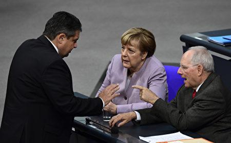 德国财政去年盈余62亿欧元,如何花这笔钱,各党派意见不一致。图为默克尔(中)与财政部长朔伊布勒(右)和经济部长加布里尔在讨论工作。(TOBIAS SCHWARZ/AFP/Getty Images)