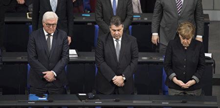 德国国会为柏林恐袭遇难者举行悼念活动,全体议员起立,默哀一分钟。右一为默克尔。(Steffi Loos/Getty Images)