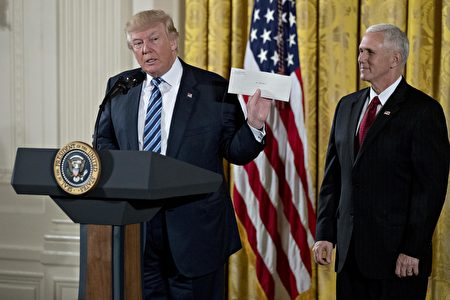 """WASHINGTON, DC - JANUARY 22: U.S. President Donald Trump holds up an envelope that was left for him in the Oval Office by former President Barack Obama next to U.S. Vice President Mike Pence, right, during a swearing in ceremony of White House senior staff in the East Room of the White House on January 22, 2017 in Washington, DC. Trump today mocked protesters who gathered for large demonstrations across the U.S. and the world on Saturday to signal discontent with his leadership, but later offered a more conciliatory tone, saying he recognized such marches as a """"hallmark of our democracy."""" (Photo by Andrew Harrer-Pool/Getty Images)"""