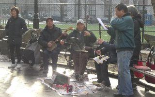 华埠哥伦布公园内时常可见老年人又弹又唱,地上放着小型麦克风,各占一隅,但是音乐声互相干扰。 (蔡溶/大纪元)