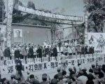 """这是一张在文革初期,1966年的批斗场面。这些人,人人低着头,背后都有怒目圆睁、押解他们的穿着绿色军装的红卫兵。台前方竖立着所有这些人的名字牌子,被冠以各种罪名予以""""打倒""""。(作者提供)"""