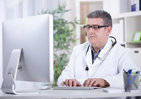 资深医生在办公室工作在计算机上(fotolia)