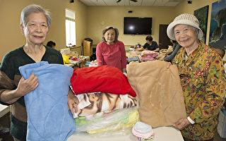 圖:聖地亞哥臺灣中心「車毯子送愛心」活動已經走過了7個年頭。很多義工都已年逾古稀。圖為年過八旬的陳賴惠美(右)和鄭阿嬤(左)拿著做好的毯子。後為召集人余洵洵。(楊婕/大紀元)