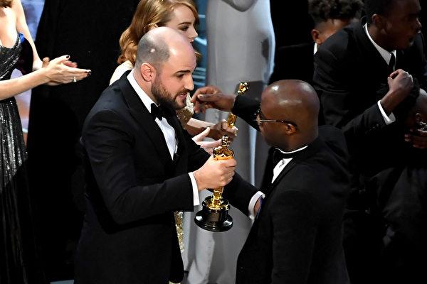 在《爱乐之城》(La La Land,台译:乐来乐爱你)被宣布获得最佳影片后,剧情大逆转,《月光男孩》(Moonlight)才是大奖得主。图为《爱乐之城》制片人向《月》片导演兼编剧交接奖杯。 (Kevin Winter/Getty Images)