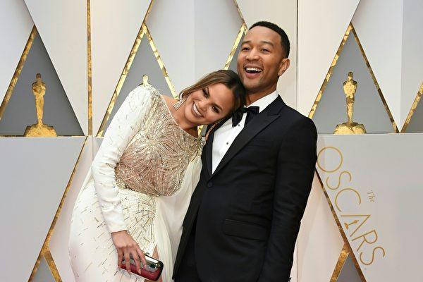 歌手约翰传奇(John Legend)与妻子克莉丝汀.泰根(Chrissy Teigen)在红毯上秀恩爱。(VALERIE MACON/AFP/Getty Images)