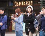 今年入冬首波寒流南下,9日氣溫明顯下降,路上行人穿著厚重衣物禦寒。(陳柏州 /大紀元)