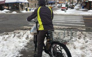 雪天送外卖的难处之一就是路面太滑,自行车根本骑不动,只好骑一段、走一段。 (于佩/大纪元)