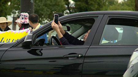洛杉磯法輪功學員拉起的橫幅吸引洛杉磯民眾的注意,開車的民眾趁著紅燈停車時,趕快拍照下來。(劉寧/大紀元)