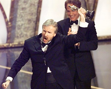"Director James Cameron raises his Oscar after winning in the Best Director Category during the 70th Academy Awards at Shrine Auditorium 23 March. Cameron won for his movie ""Titanic."" Behind Cameron is presenter Warren Beatty. (ELECTRONIC IMAGE) AFP PHOTO Timothy A. Clary (Photo credit should read TIMOTHY A. CLARY/AFP/GettyImages)"