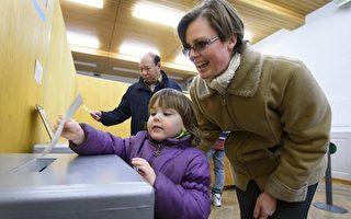 瑞士周日(2月12日)举行公投,通过了放宽第三代移民入籍条件的法案。这将使在瑞士土生土长的第3代移民自动成为公民。图为选民进行投票。(FABRICE COFFRINI/AFP/Getty Images)