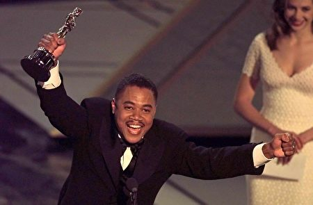 "LOS ANGELES, UNITED STATES: Actor Cuba Gooding, Jr holds up his Oscar after winning the Best Supporting Actor Award for his role in ""Jerry Maguire"" during the 69th Academy Awards 24 March. The awards are being held in the Shrine Auditorium. (ELECTRONIC IMAGE) Timothy A. Clary (Photo credit should read TIMOTHY A. CLARY/AFP/Getty Images)"