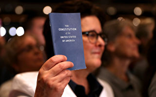 2016年11月6日在美國新罕布什爾州,一位參加大選集會的美國人手舉美國《憲法》簡裝本。( Justin Sullivan/Getty Images)