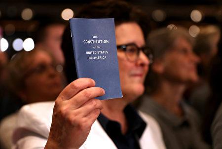 2016年11月6日在美国新罕布什尔州,一位参加大选集会的美国人手举美国《宪法》简装本。( Justin Sullivan/Getty Images)