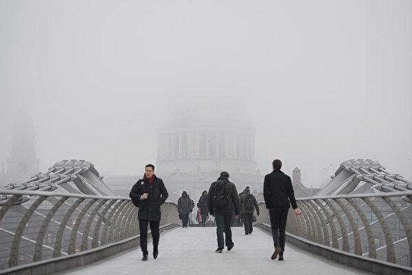 1月23日,浓雾笼罩伦敦,站在千禧桥上,不远处的圣保罗大教堂只能看到一个模糊的轮廓。(Leon Neal/Getty Images)