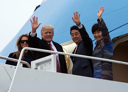 川普夫妇和安倍夫妇在空军一号舱门向群众挥手致意。(NICHOLAS KAMM/AFP/Getty Images)