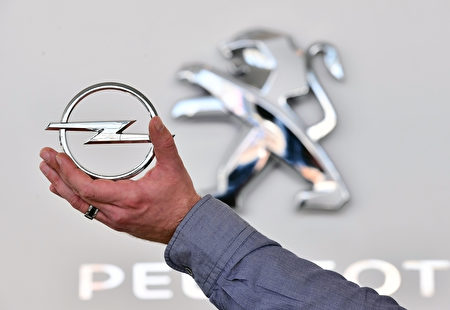 DARMSTADT, GERMANY - FEBRUARY 15:  In this photo illustration, the Peugeot logo is seen behind an Opel hood ornament on February 15, 2017 in Darmstadt, Germany. PSA Peugeot Citroen is reportedly seeking to buy German automaker Opel from its parent company General Motors. The acquisition would require the consent of the German government, which would likely mean negotiations over job safeguards for Opel workers. General Motors has owned Opel since 1929.  (Photo by Illustration by Thomas Lohnes/Getty Images)