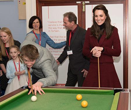 2月22日,英国剑桥公爵夫人、凯特王妃访问威尔士一家儿童慈善机构。凯特身穿一袭深红大衣打撞球。(Photo by Paul Edwards - WPA Pool/Getty Images)