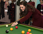 2月22日,英国剑桥公爵夫人、凯特王妃访问威尔士一家儿童慈善机构。凯特身穿一袭深红大衣打台球。(Photo by Paul Edwards - WPA Pool/Getty Images)