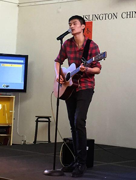 协会执行委员王本彦为观众吉他伴唱自己的原创歌曲。(文沁/大纪元)