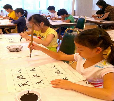 学生写毛笔字。 (明慧文化艺术中心提供)