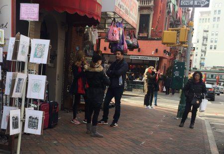 """尽管风声鹤鸣,假货小贩并没有因此""""收手"""",只是人数减少。图中左侧一名小贩正在向西人游客兜售假货。 (蔡溶/大纪元)"""